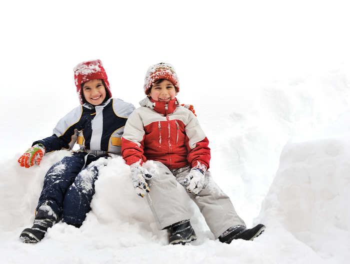 Two children playing in the snow.