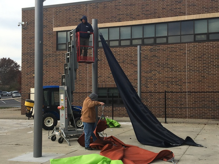 Custodians take down sails at The Lab.