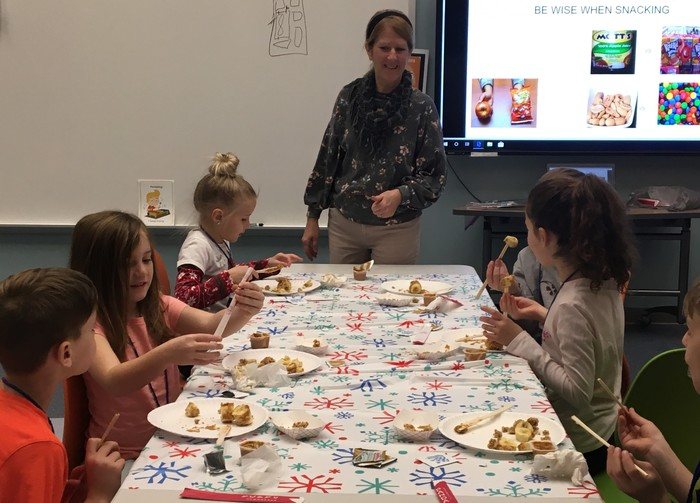 2nd graders make fruit sushi as a healthy snack.