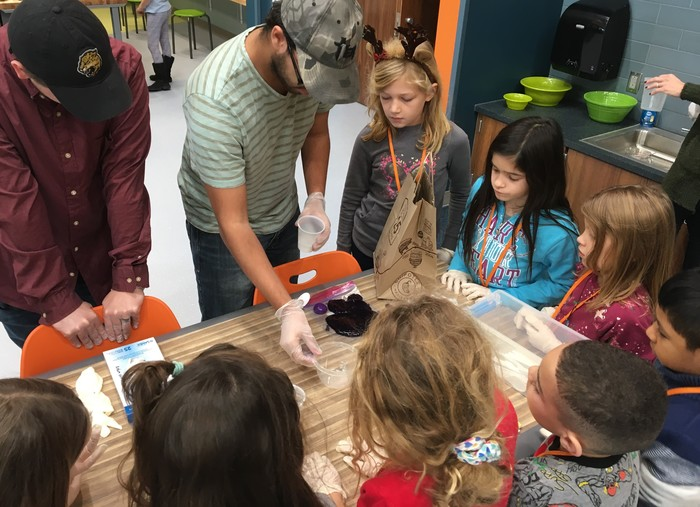 College students make slime with 2nd graders.
