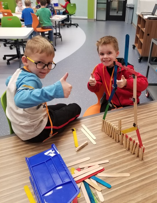 Students use objects to create different types of bridge structures.