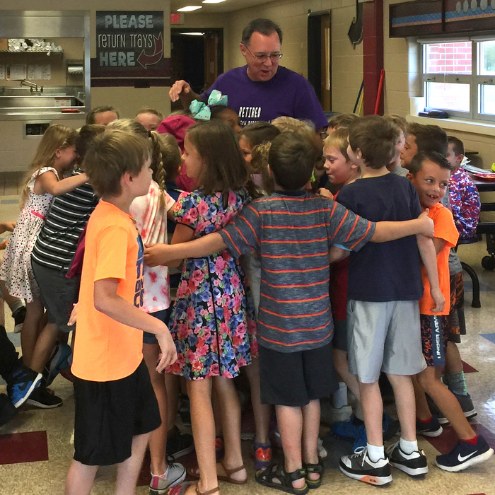 Mr. Adams gets a group hug on his last day at Van Buren.