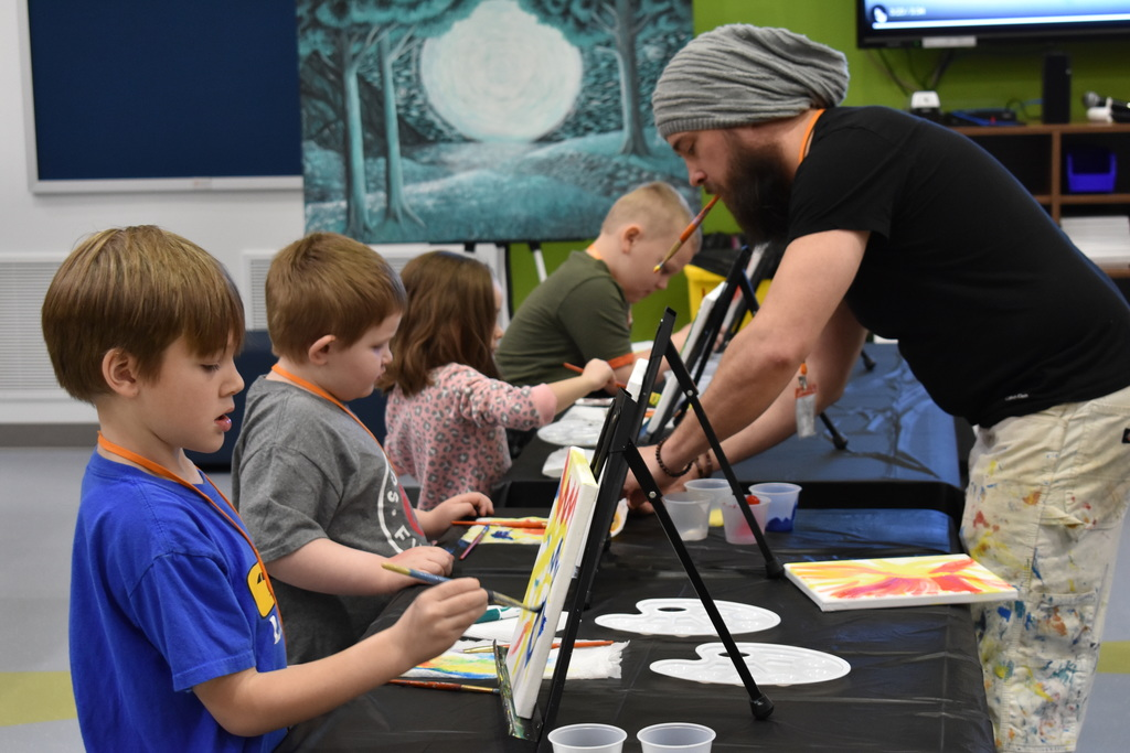 James instructing kids to paint with canvas and easels