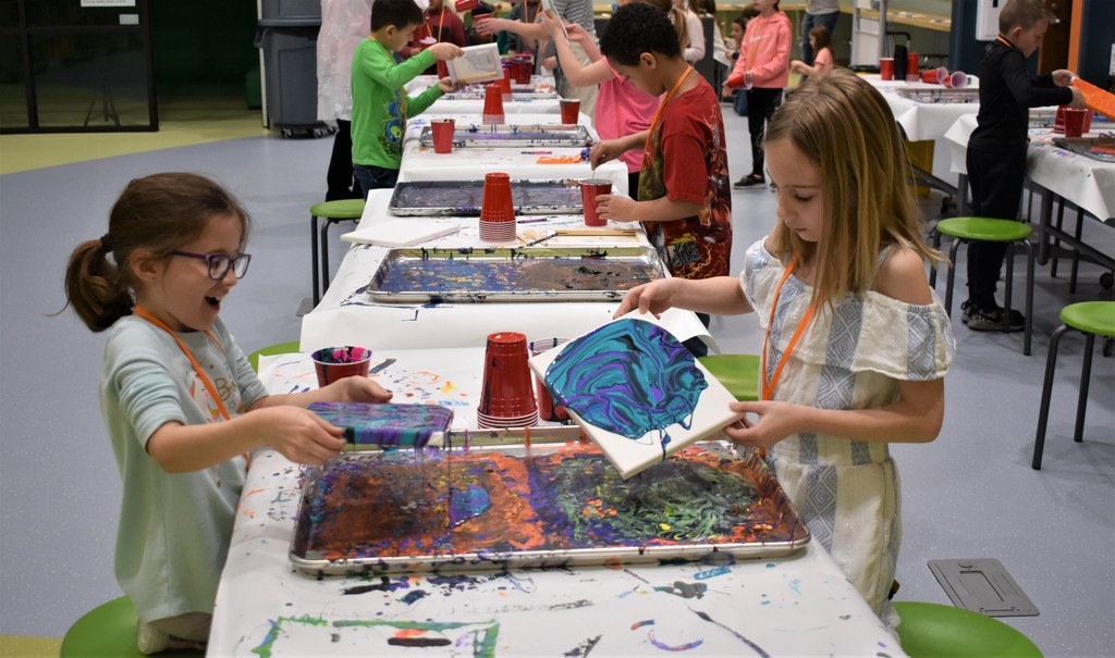 kids paint pouring with canvases