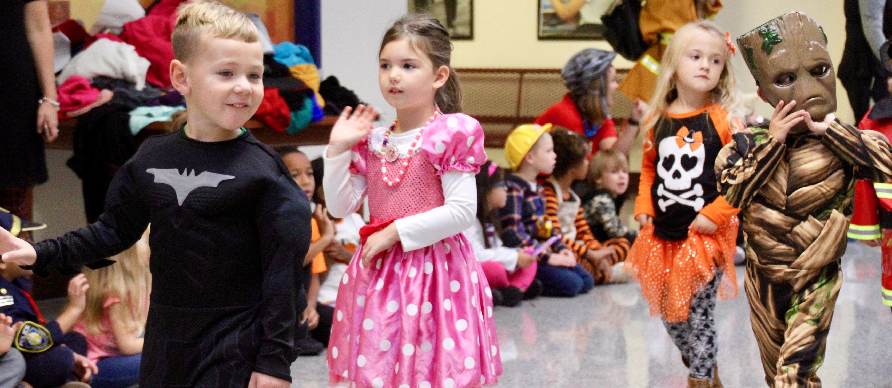 Students from Little Quakers Academy preschool parade their Halloween costumes through Clarks Creek at the start of the Halloween school day.