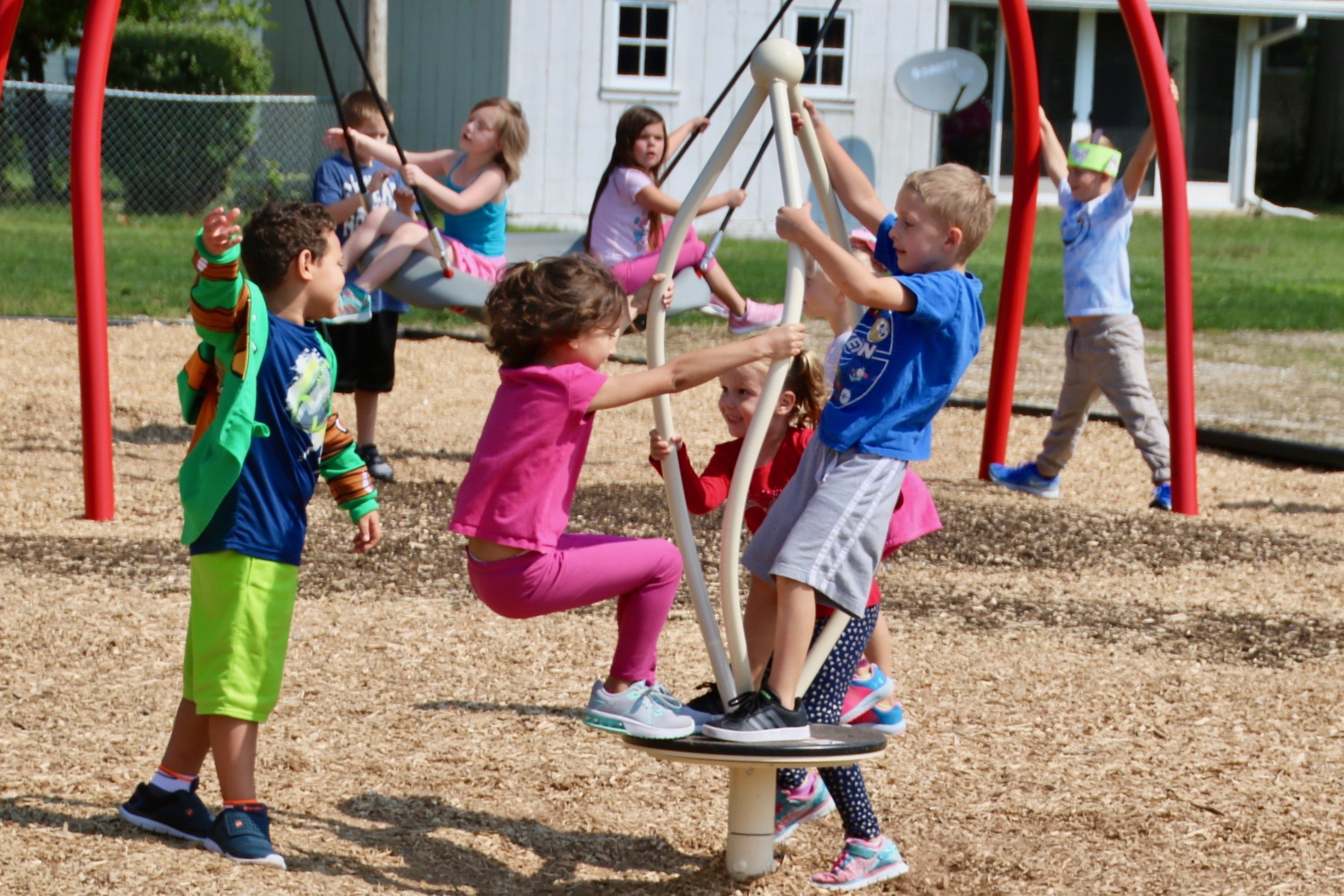 Students playing on new playground equipment on a sunny summer day