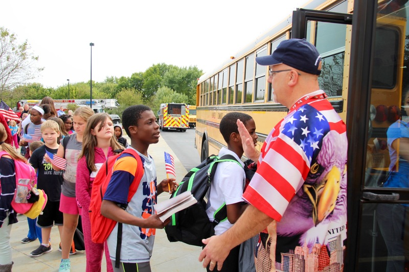 At dismissal, students from each class lined the front sidewalk with flags, while everyone left in silence.
