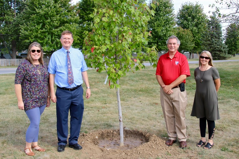 Katie Chamness, Scott Flood and Jessica Elston of the Plainfield School Board, pose with Brad DeHoff in front of his newly planted tree of honor.
