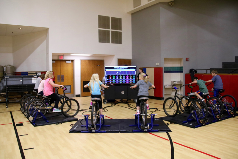 On stationary bikes, students ride different courses requiring varying degrees of exertion. A massive monitor helps them chart their progress.