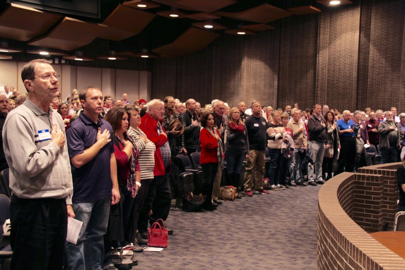 The sound of a full auditorium, reciting the Pledge of Allegiance in one voice.