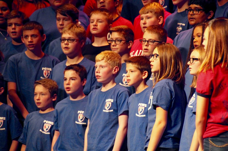 "The 7th grade choirs came together to perform several patriotic songs, included a sing-along version of ""God Bless America."""
