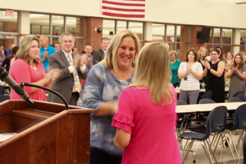 Ann Mennonno shakes hands with School Board President Jessica Elston, while her peers give her a standing ovation