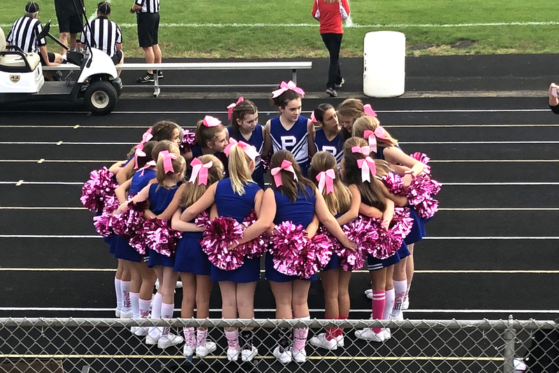 8th grade cheerleaders huddle with their pink pom pons, borrowed from the PHS squad